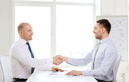 Two smiling businessmen shaking hands in office Stock Photo