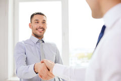 Two smiling businessmen shaking hands in office Royalty Free Stock Images