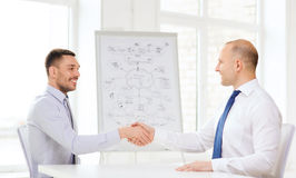 Two smiling businessmen shaking hands in office Stock Images