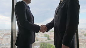 Two smiling businessmen shaking hands. Standing by windows in an office with panoramic view on city stock footage
