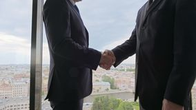 Two smiling businessmen shaking hands. Standing by windows in an office with panoramic view on city stock video footage