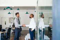 Two smiling businessmen shaking hands together after an office meeting royalty free stock images