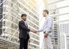 Two smiling businessmen shaking hands together. Stock Photos