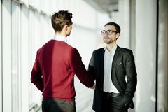 Two smiling businessmen shaking hands together while standing by windows in an office boardroom overlooking the city royalty free stock photography