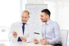 Two smiling businessmen with tablet pc in office Stock Photography