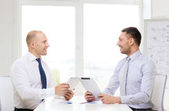 Two smiling businessmen with tablet pc in office Royalty Free Stock Images