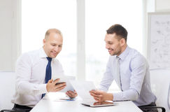 Two smiling businessmen with tablet pc in office Stock Image