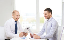 Two smiling businessmen with tablet pc in office Stock Photo