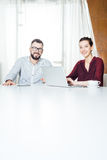 Two smiling businesspeople sitting and using laptop in meeting room Stock Photo