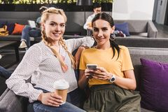 two smiling businesswomen with coffee and smartphone at modern coworking stock image