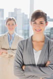 Two smiling businesswomen looking at camera with arms crossed Stock Images