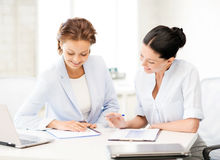 Two smiling businesswomen working in office Stock Photo