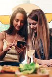 Two smiling Caucasian female friends watching photos and videos on smartphone sitting in coffee shop having lunch break Royalty Free Stock Photo