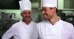 Two smiling chefs giving ok sign to camera. In a commercial kitchen stock video footage