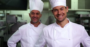 Two smiling chefs giving thumbs up to camera. In a commercial kitchen stock video footage