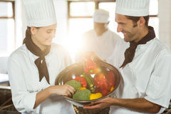 Two smiling chefs holding a bowl of vegetable Stock Photos
