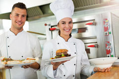 Two smiling chefs in kitchen Stock Photos
