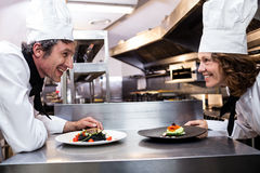Two smiling chefs leaning on counter with meal plates Stock Images