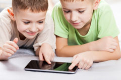 Two smiling child boys playing games or surfing internet on tabl Royalty Free Stock Photos