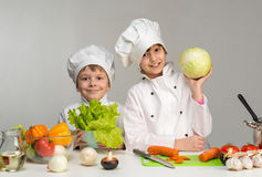 Two smiling children-cooks by the table with vegetables Royalty Free Stock Photo