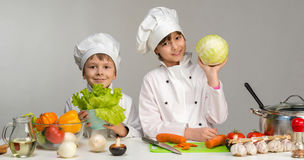 Two smiling children-cooks by the table with vegetables Stock Image