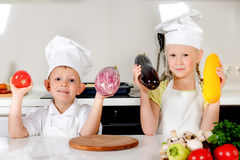 Two smiling children holding up fresh vegetables Royalty Free Stock Photos