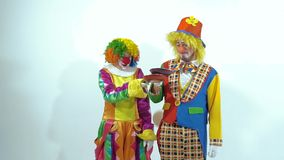 Two smiling circus clowns throwing up toy-pancakes, they cannot catch both of them stock video