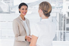 Two smiling colleagues shaking hands Royalty Free Stock Photo