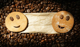 Two smiling cookies on package label with roasted coffee beans. Two smiling cookies on top of mint wrapping paper on roasted coffee beans Stock Photo