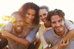 Two smiling couples piggybacking outdoors, close up Stock Photography