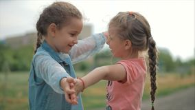 Two smiling, curly, cute sisters baby-girls hug tightly each other. Happy childhood, positive emotions, true feelings. stock footage