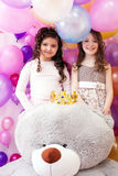 Two smiling cute sisters and big teddy bear Royalty Free Stock Photography
