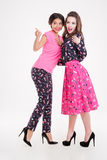 Two smiling cute young women talking and pointing away Royalty Free Stock Photos