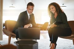 Two smiling diverse businesspeople working on a laptop together stock image