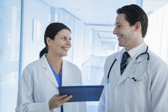 Two smiling doctors looking and holding a medical record in the hospital Royalty Free Stock Photography