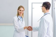 Two smiling doctors in white coats shaking hands. In hospital royalty free stock photos