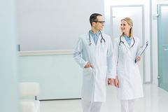 Two smiling doctors in white coats with stethoscopes and diagnosis. In hospital stock photos