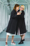 Two smiling elegant woman dressed in coat looking at smart phone Stock Photo