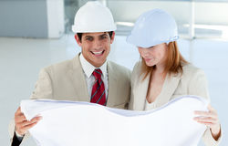 Two smiling engineers studying blueprints Stock Photos