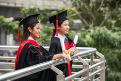 Two smiling female Asian students in graduation gown royalty free stock photo
