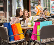 Two smiling female friends driniking coffee and taking selfie. After shopping Stock Photography