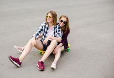 Two smiling female friends having fun riding yellow longboard on the street. Friendship concept stock photography