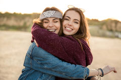 Two smiling female friends hugging each other royalty free stock images