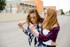 Two smiling female friends hugging each other on the street. Holidays, vacation, love and friendship concept stock photography