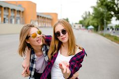 Two smiling female friends hugging each other on the street. Holidays, vacation, love and friendship concept stock images