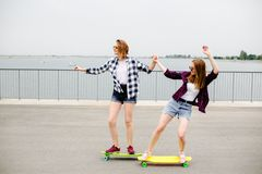 Two smiling female friends learning riding longboard with helping each other. Friendship concept stock photo