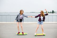 Two smiling female friends learning riding longboard with helping each other. Friendship concept royalty free stock photo