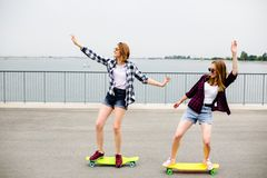 Two smiling female friends learning riding longboard with helping each other. Friendship concept royalty free stock photos