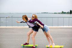 Two smiling female friends learning riding longboard with helping each other. Friendship concept royalty free stock image
