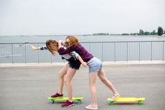 Two smiling female friends learning riding longboard with helping each other. Friendship concept royalty free stock images